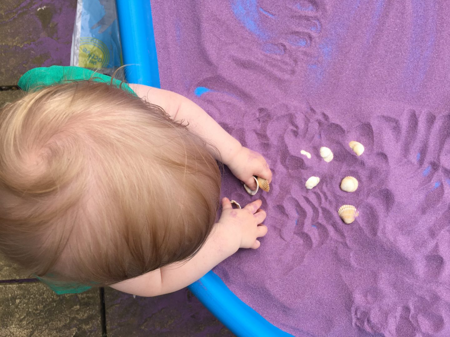 M playing with purple sand