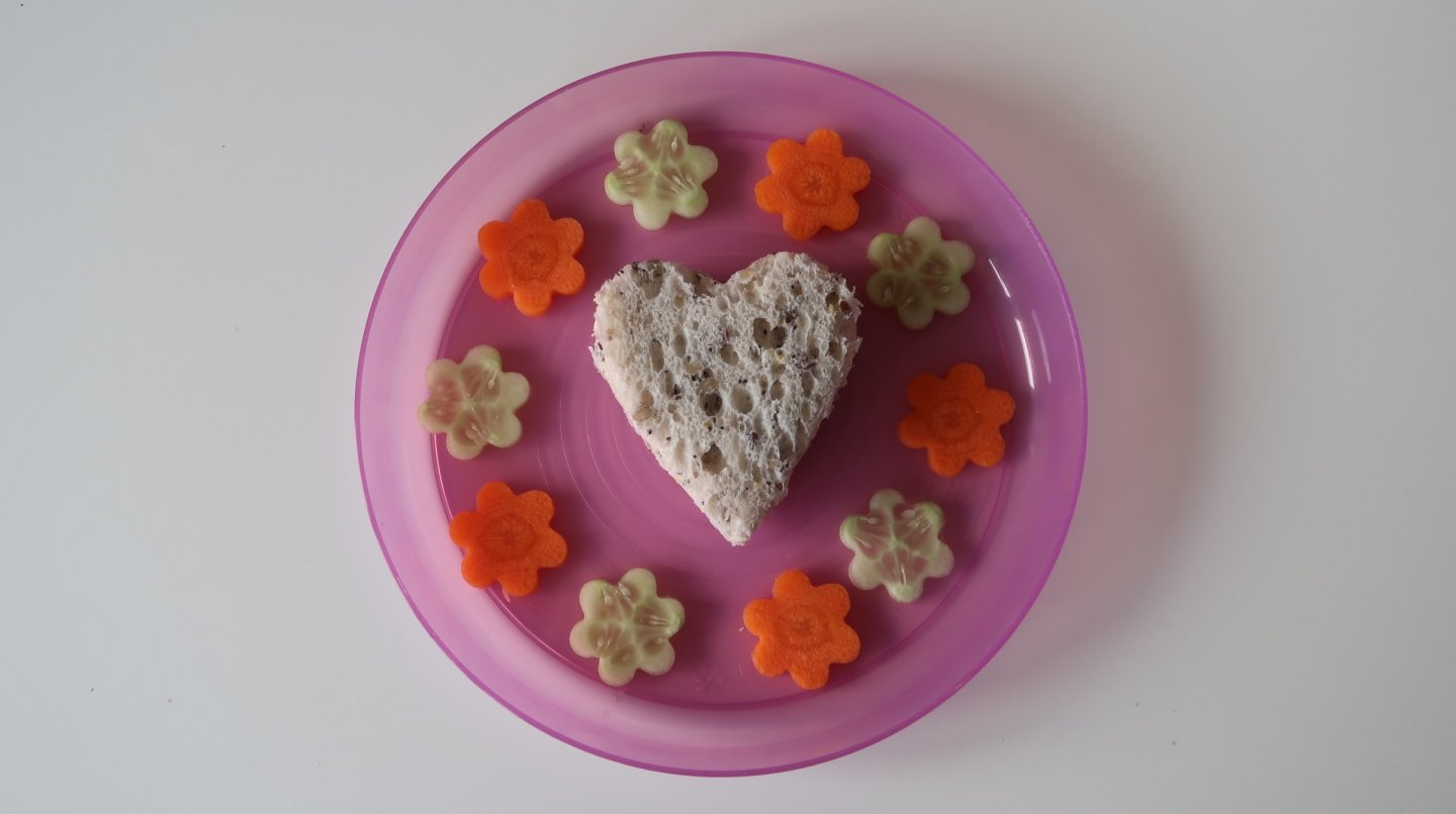 A heart shaped ham and cheese sandwich surrounded by carrot and cucumber flowers.