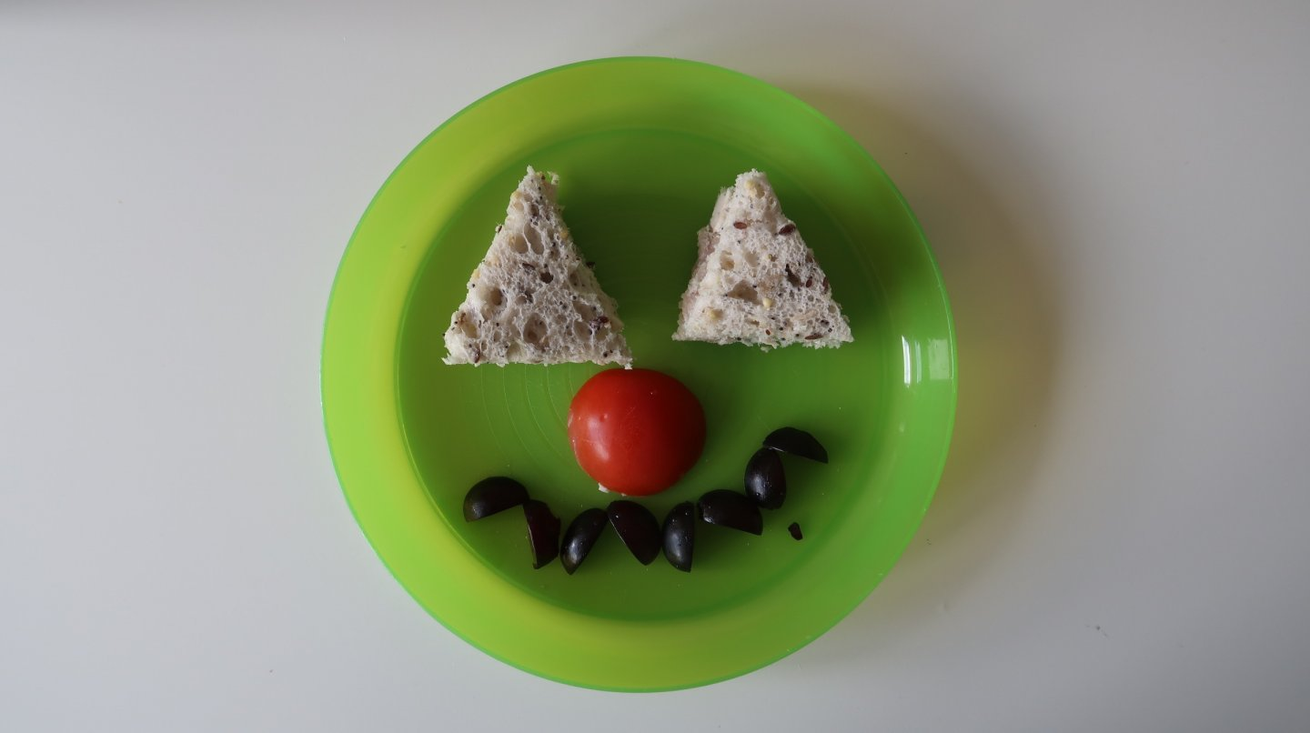 Monster face with triangular cheddar cheese sandwich, tomato nose and black olive teeth.