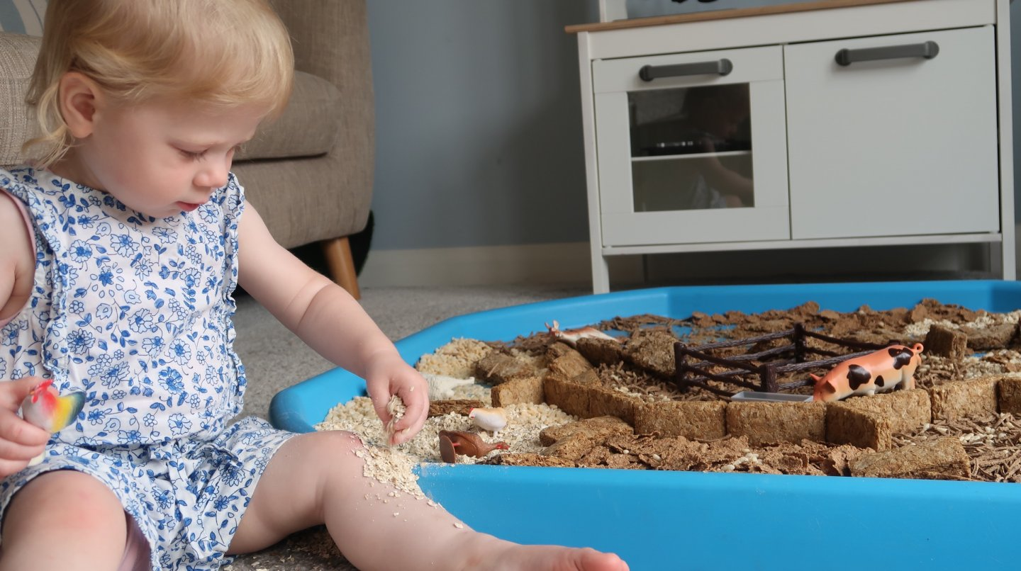 EYFS sensory cereal tuff tray. Toddler sprinkling porridge oats on her leg.