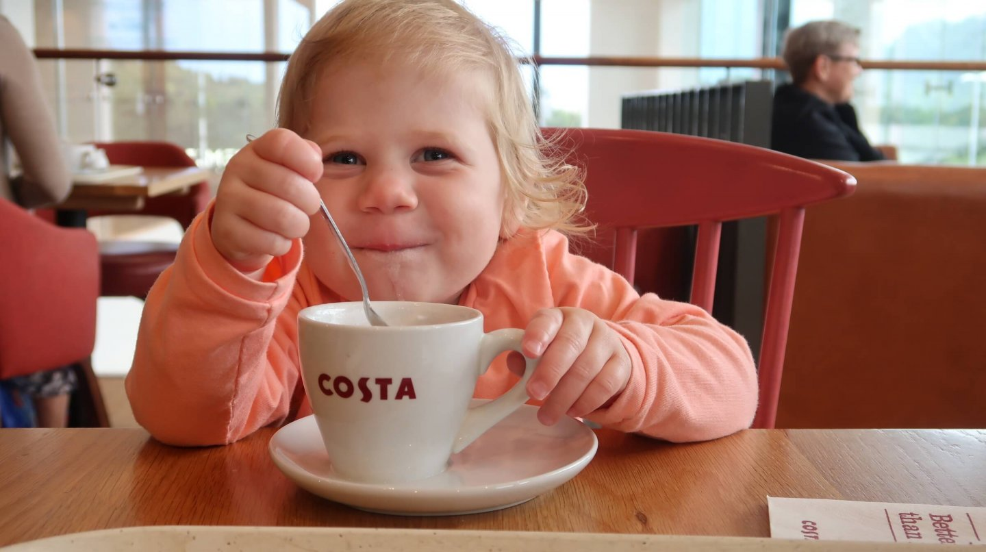 M enjoying a Costa babyccino with a very cheeky smile.