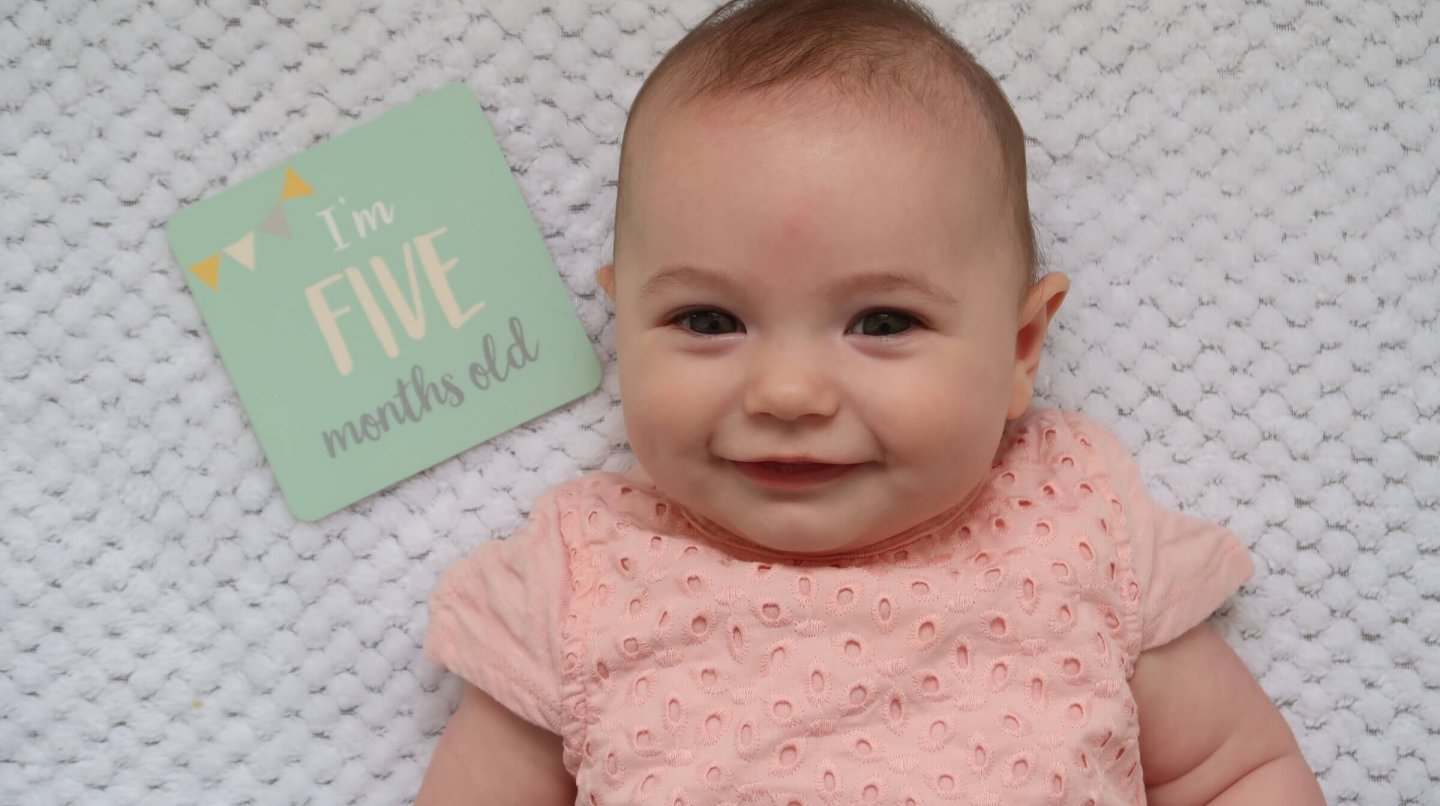 B with her five month milestone card.