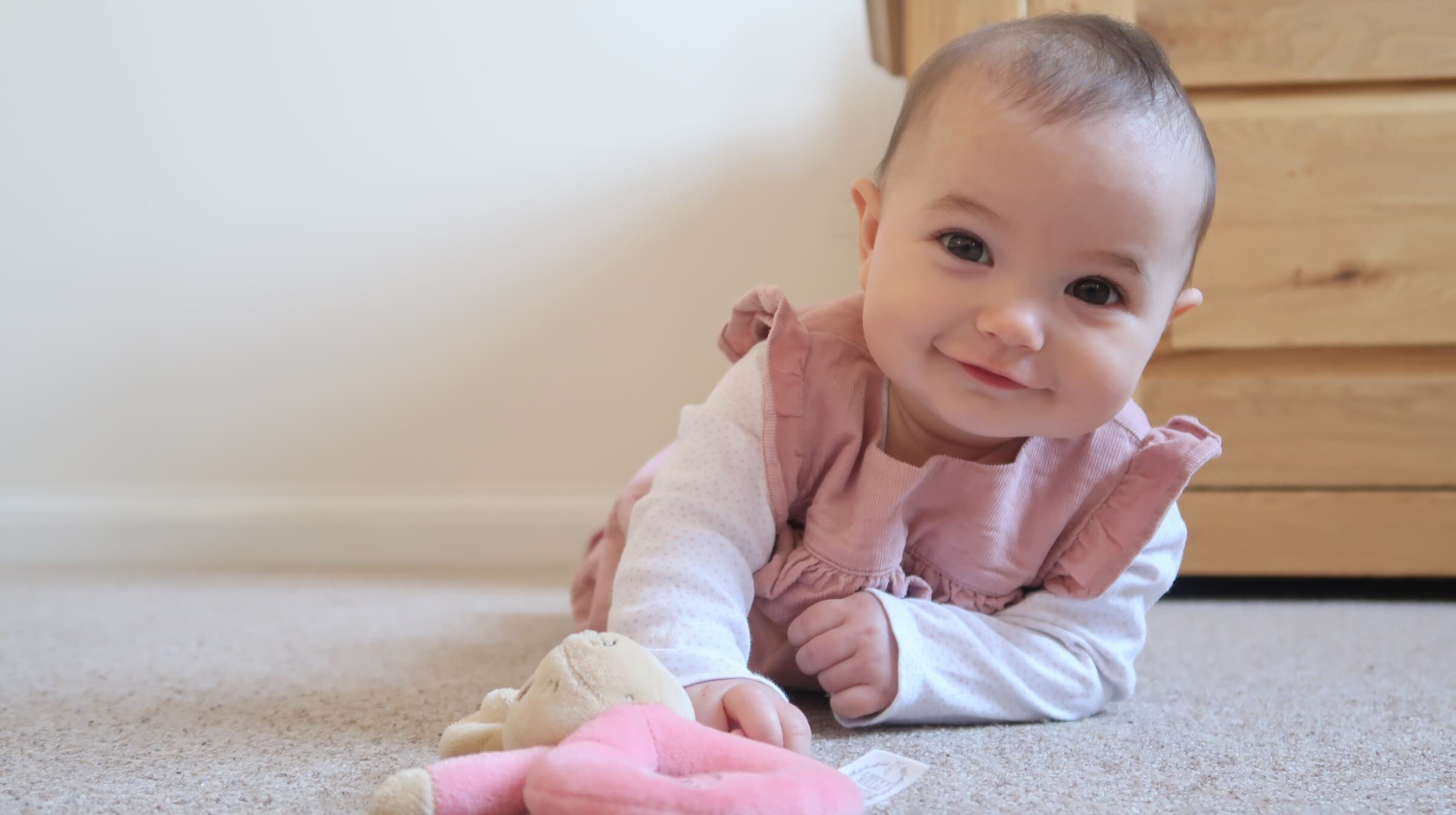 B wearing a pink dress, lying on her tummy, smiling at the camera and reaching for her plush pink rabbit rattle.