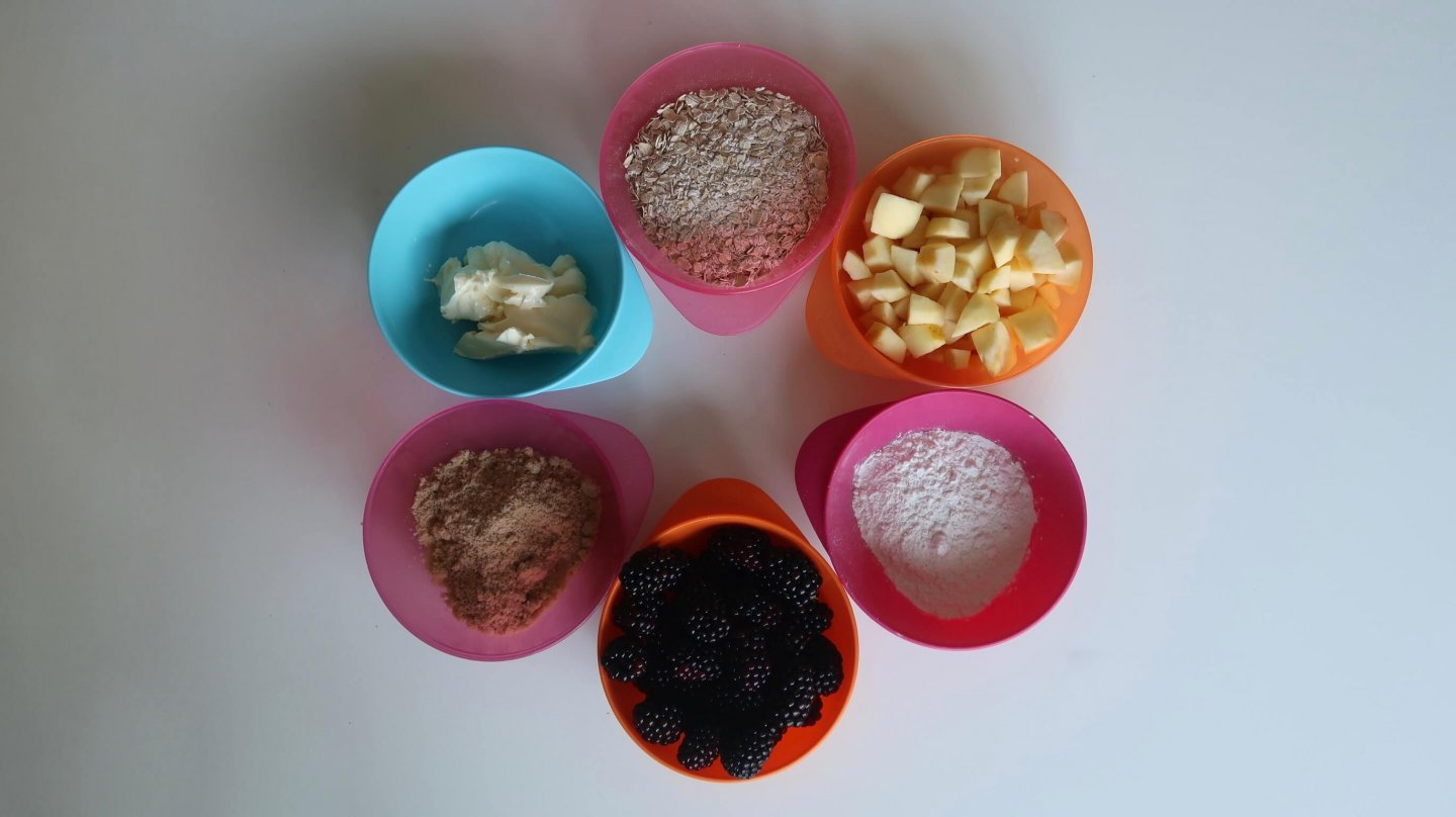 Gluten Free Gruffalo Crumble Ingredients - butter, brown sugar, blackberries, gluten free flour, chopped apples and porridge oats, in colourful plastic bowls arranged in a circle.