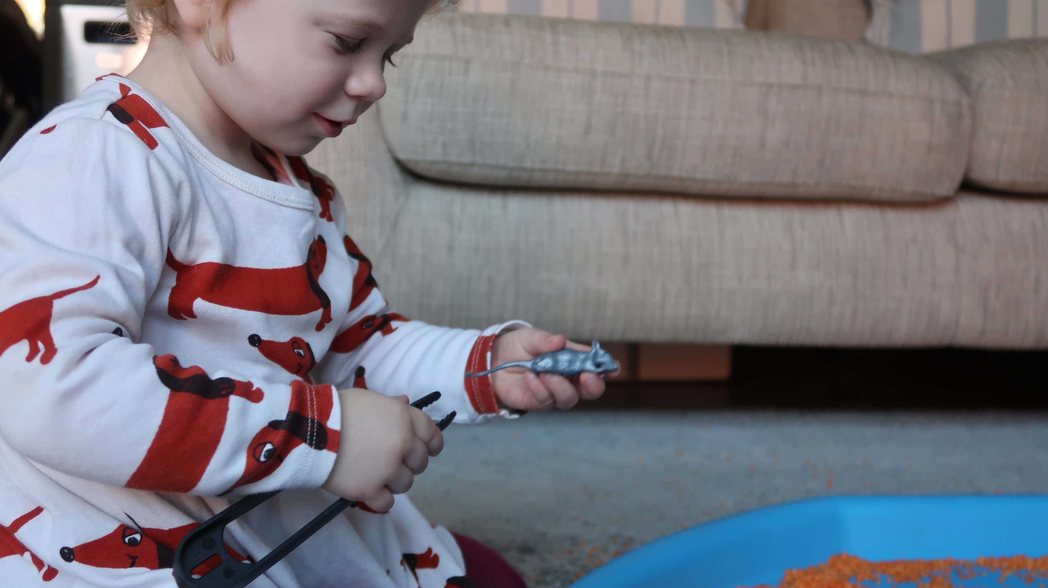 Activities for Encouraging Pencil Grip - M holding a small plastic toy mouse and plastic tongs.
