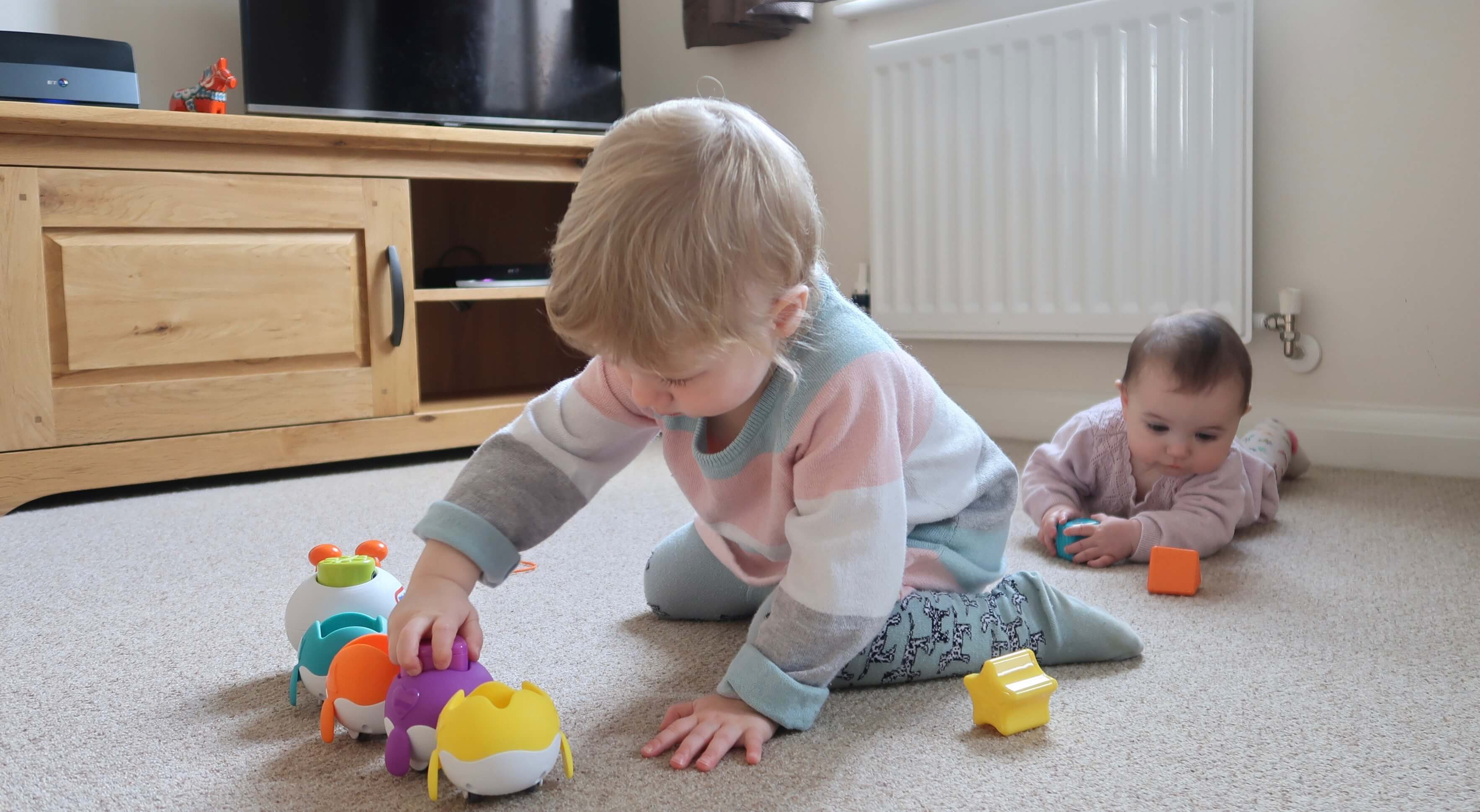 Little Tikes Fantastic Firsts Singing Sorter Review - M puts shapes into the sorter as B plays with some of the pieces