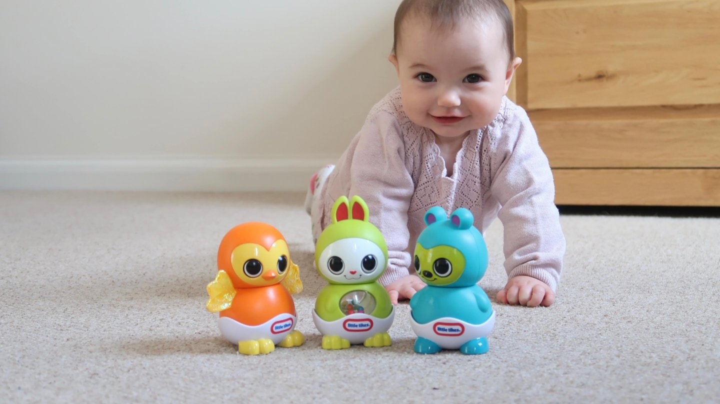 Little Tikes Fantastic Firsts Sleepy Stacker Review - B lies in a crawling position behind the three toys, coloured orange, green and blue.