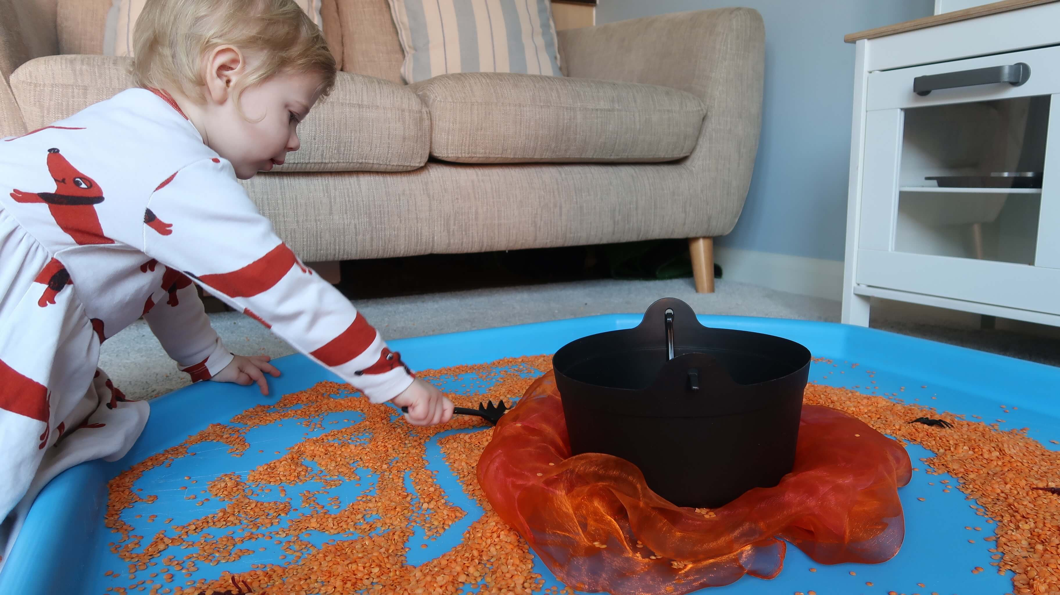 Room on the Broom Tuff Spot - M scooping red split lentils into a plastic cauldron