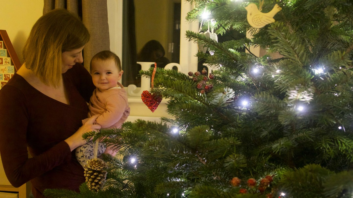 What to buy your second baby for Christmas - B helping to put decorations on the Christmas tree.