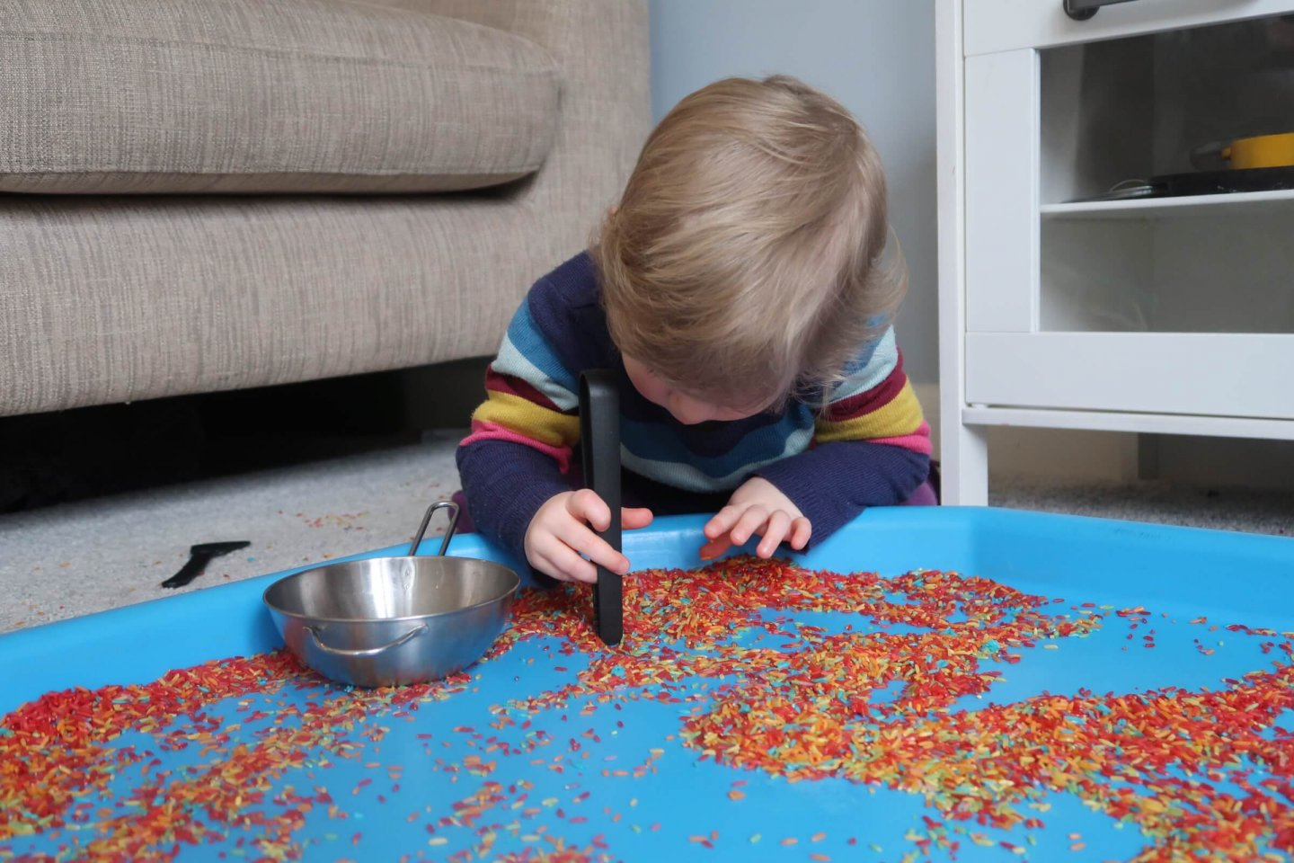 Development of fine motor skills using rainbow rice.
