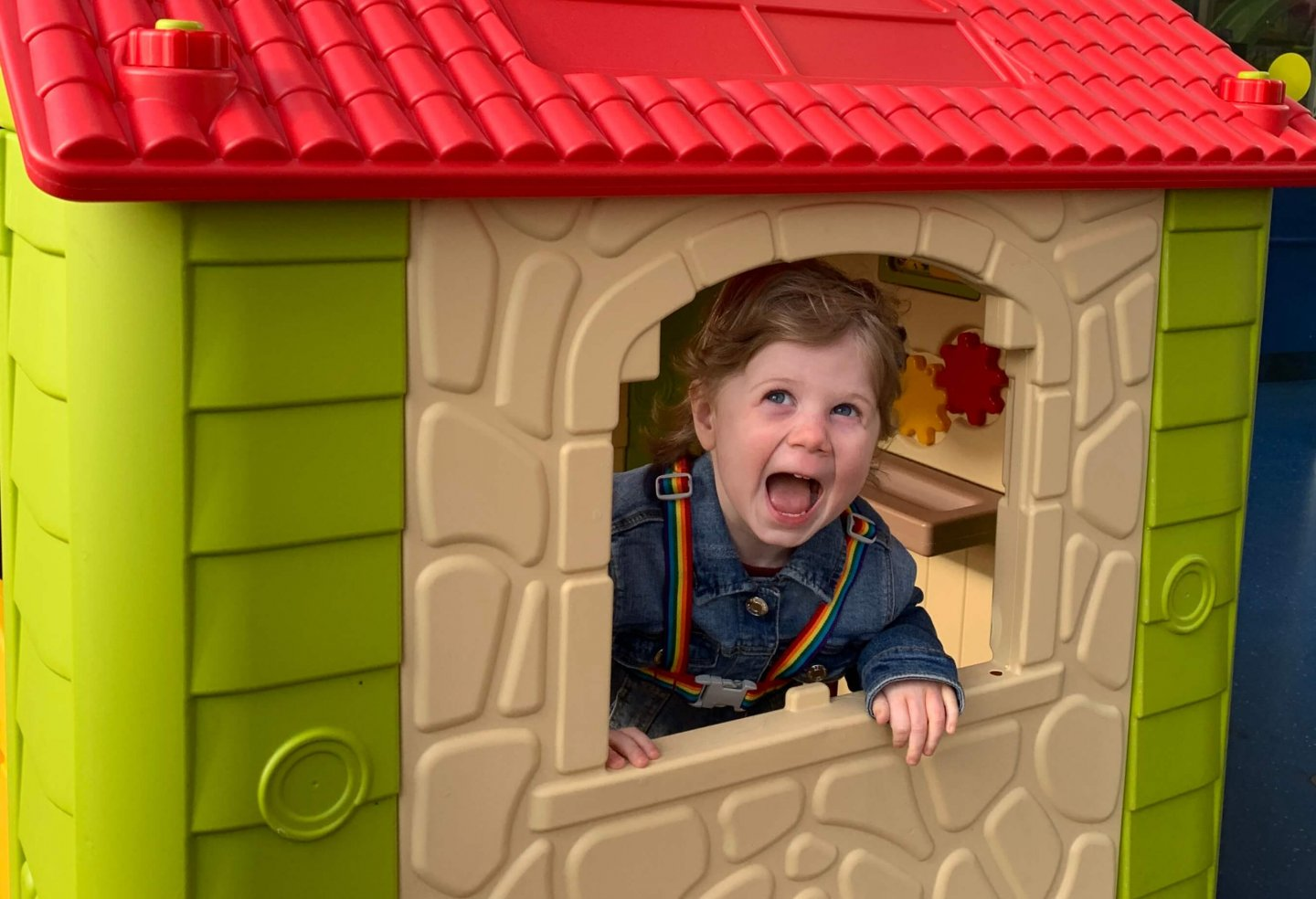 M grinning through the window of a play house.