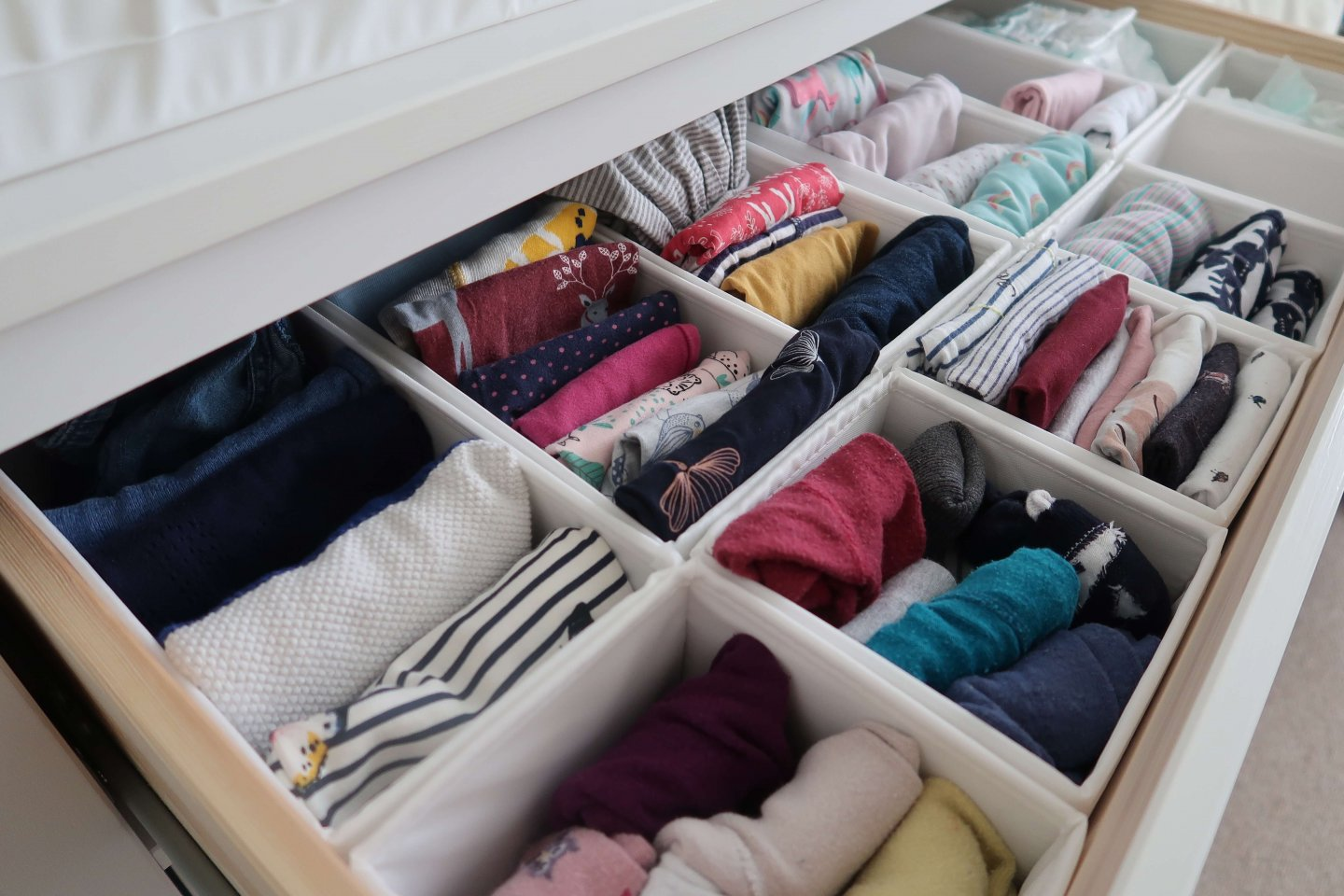Using the KonMari folding technique to organise baby and toddler clothing.